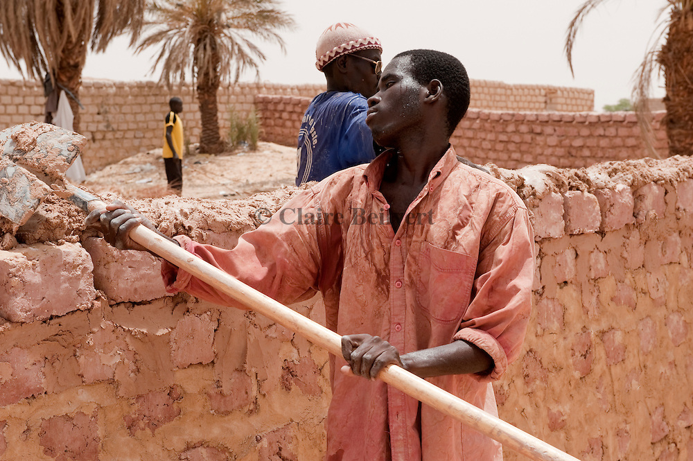 """A young African migrants from Mali working at the contruction of a wall in Dirkou. It is a very hard job, the weather temparature is extreme : more than 50 °C. He is what other migrants call a """"stranded"""": He earns enough mony just to eat and has no possibility to earn more to leave and go to Libya. This situation turns the trip of a migrant into a nightmare."""