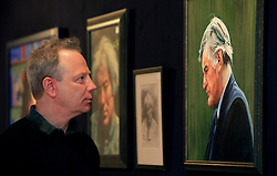 © Licensed to London News Pictures 08/04/2013.Artist Peter Edwards poses infront of his portraits of Ted Hughes and Seamus Heeney, at the Bonhams Auction House in London. A selection of his paintings will be sold as part of the 'Roy Davids Collection Part III: Poetry: Poetical Manuscripts and Portraits of Poets', on 10th April and 8th May, at Bonhams, London. .London, UK.Photo credit: Anna Branthwaite