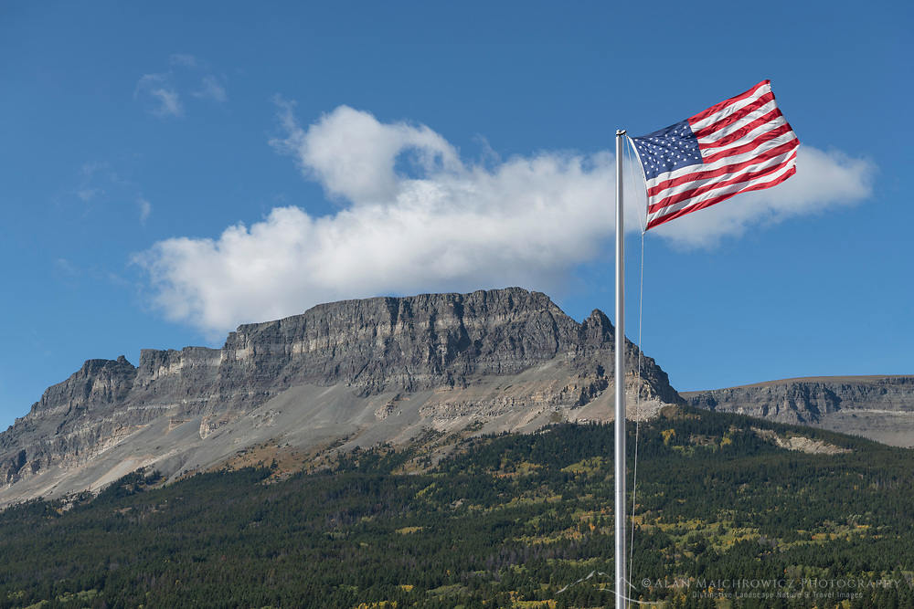 American Flag at Saint Mary Lake visitor center. Singleshot Mountain is in the distance. Glacier National Park