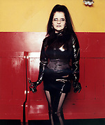 Goth woman holding a bottle posing standing in front of red and yellow wall.