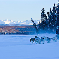 A dog musher takes his team across frozen Fish Lake near Talkeetna, Alaska. Talkeetna is a main base for climbers preparing to scale Denali or Mt. McKinley, as well as a winter and summer playground for outdoor enthusiasts.