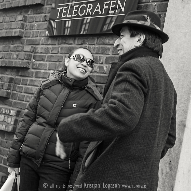 Man and a woman chating under a sign from Telegrafen in central Bergen