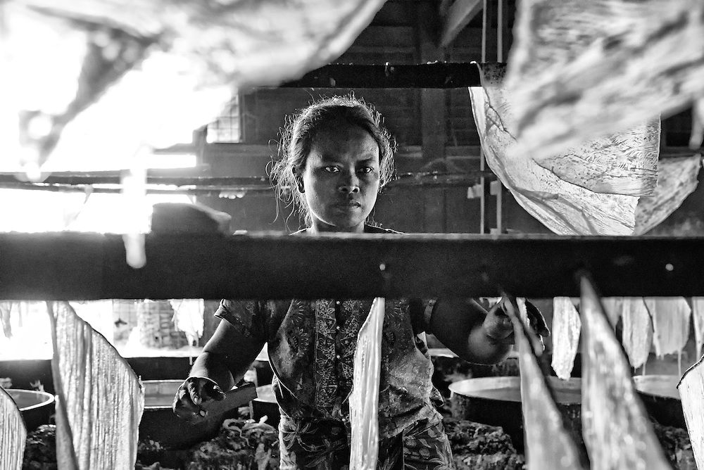 A woman from Non Shae, Myanmar endure relentless heat and temperatures daily with steaming pots of tofu to make tofu paper.