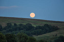 © Licensed to London News Pictures. 03/07/2015. Malham, UK. Picture shows last nights full moon over farm land in the village of Malham. Hailstones the size of golf balls and fierce lightning storms battered homes yesterday but blue skies are set to return today . Temperatures are set to soar to 29C (82F) today. Photo credit : Andrew McCaren/LNP