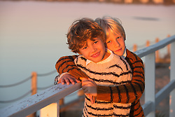 twin boys hugging outdoors on a deck overlooking the bay in the Hamptons at sunset