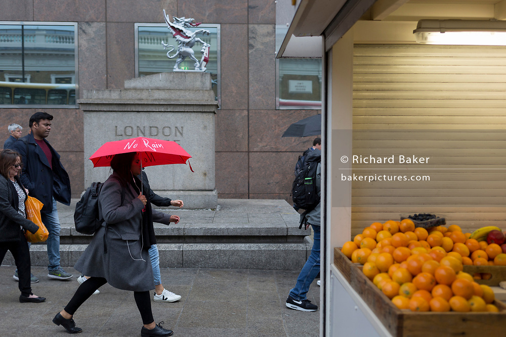 During a sprint shower, a lady carries an umbrella with the words No Rain while walking past fresh oranges on sale at a stall on London Bridge during the evening rush-hour, from the City southwards to Southwark, on 3rd May, in London, England