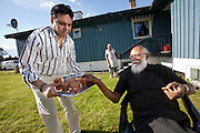The Qureshi family of Lorenskog, Norway, an Oslo suburb. In his backyard after a weekend lunch, Nasrullah Qureshi, 51, serves chai tea to his father-in-law, U.S. Sakhi, 74. Model-Released.