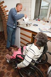 Wheelchair user with Spina Bifida in her kitchen watching her father making tea.