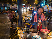 "21 DECEMBER 2015 - BANGKOK, THAILAND: A food vendor with her cart on the street in front of Pak Khlong Talat, also called the Flower Market. The market has been a Bangkok landmark for more than 50 years and is the largest wholesale flower market in Bangkok. A recent renovation resulted in many stalls being closed to make room for chain restaurants to attract tourists. Now Bangkok city officials are threatening to evict sidewalk vendors who line the outside of the market. Evicting the sidewalk vendors is a part of a citywide effort to ""clean up"" Bangkok.       PHOTO BY JACK KURTZ"