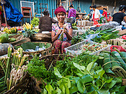 11 OCTOBER 2016 - UBUD, BALI, INDONESIA:   A vendor bundles lemongrass she's selling in her market stall in the morning market in Ubud. The morning market in Ubud is for produce and meat and serves local people from about 4:30 AM until about 7:30 AM. As the morning progresses the local vendors pack up and leave and vendors selling tourist curios move in. By about 8:30 AM the market is mostly a tourist market selling curios to tourists. Ubud is Bali's art and cultural center.    PHOTO BY JACK KURTZ