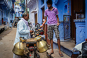 A milkman sells some milk to a boy at the door to his home. In Bundi, milkmen usually sell milk in the early morning. They either stope at people's doors or at specific places where the people come and meet them.