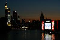 Feature Public Viewing Frankfurt          Auf einer schwimmende Leinwand wird am Mainufer in Frankfurt das Spiel Argentinien gegen Elfenbeinkueste uebertragen. Tausende Zuschauer beobachten das Spiel vom Ufer aus. Im Hintergrund die Skyline von Frankfurt.