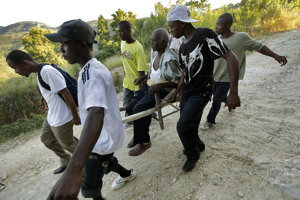 A man is brought down the mountainside above Carrefour, Haiti, by family and friends on a makeshift stretcher after he started to complain about extreme abdominal pain.  With no ambulances, this is the only way for patients to get the the hospital in an emergency.