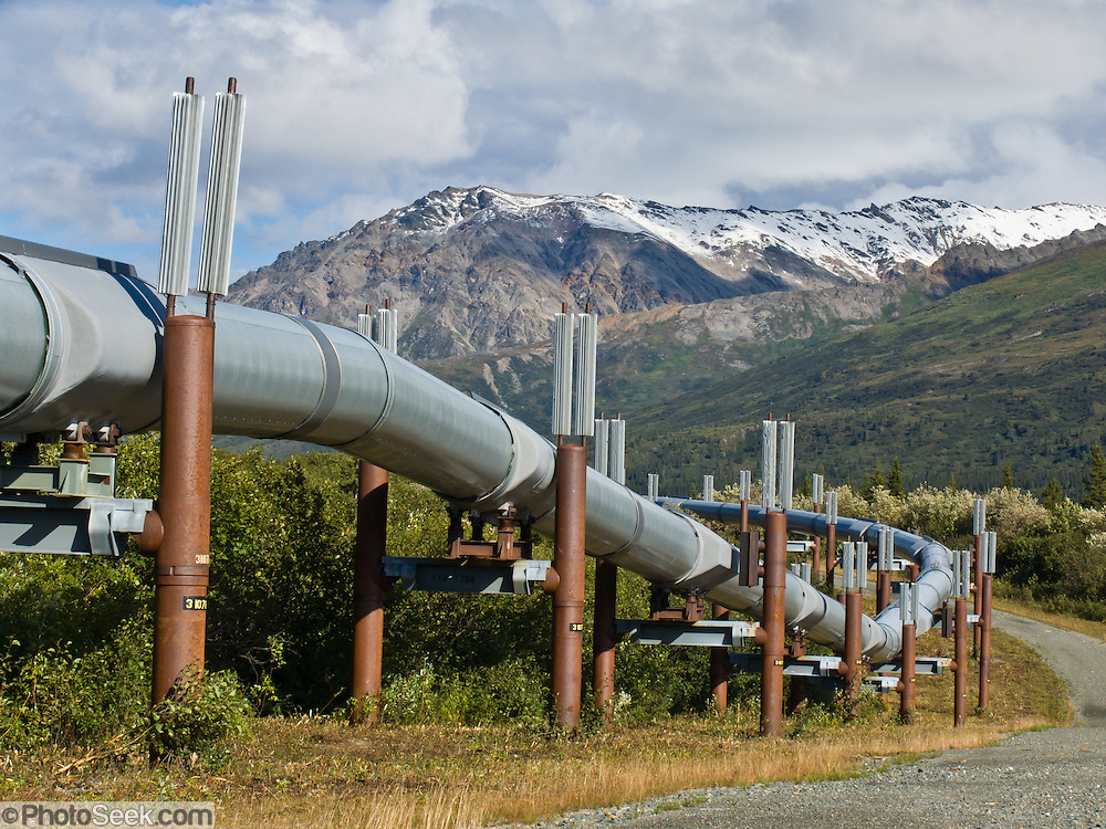 The Trans Alaska Pipeline (or Alyeska Pipeline) crosses the Alaska Range and conveys crude oil 800 miles (1287 km) from Prudhoe Bay to Valdez, Alaska, USA. Heat Pipes conduct heat from the oil to aerial fins to avoid melting the permafrost. The 48-inch diameter (122 cm) pipeline is privately owned by the Alyeska Pipeline Service Company. The Trans Alaska Pipeline System (TAPS) includes The Pipeline, several hundred miles of feeder pipelines, 11 pump stations, and the Valdez Marine Terminal. Environmental, legal, and political debates followed the discovery of oil at Prudhoe Bay in 1968. After the 1973 oil crisis caused a sharp rise in oil prices in the United States and made exploration of the Prudhoe Bay oil field economically feasible, legislation removed legal challenges and the pipeline was built 1974-1977. Extreme cold, permafrost, and difficult terrain challenged builders. Tens of thousands of workers flocked to Alaska, causing a boomtown atmosphere in Valdez, Fairbanks, and Anchorage. Oil began flowing in 1977. The pipeline delivered the oil spilled by the huge 1989 Exxon Valdez oil tanker disaster, which caused environmental damage expected to last 20-30 years in Prince William Sound.