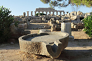 Stone basin of an olive oil press, on the acropolis of the ancient ruined Greek city of Selinunte, Sicily, Italy. In the distance is Temple C, built 550 BC, with a peristyle of 6 x 17 Doric columns, 14 of which were re-erected in 1925-27 along with a section of the entablature. It was dedicated to Apollo and is thought to have been used as an archive. Selinunte was founded in 628 BC and was an important Greek colony, home to up to 100,000 people at its peak and abandoned in 250 BC. The city consists of an acropolis housing 2 main streets and 5 temples, 3 other hills with housing and temples and 2 necropoleis. Picture by Manuel Cohen