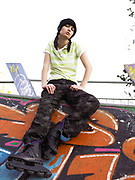 A young woman sat on railing wearing rollerblades looking down at camera.