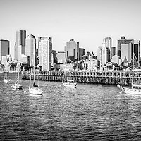 Boston skyline picture in black and white with Boston Harbor, downtown Boston skyscrapers, Port of Boston pier and sailboats.