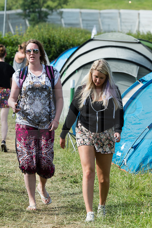 © Licensed to London News Pictures. 25/06/2015. Pilton, UK. Festival atmosphere at Glastonbury Festival 2015 on Thursday Day 2 of the festival.  The wall can be seen in the background. This years headline acts include Kanye West, The Who and Florence and the Machine, the latter having been upgraded in the bill to replace original headline act Foo Fighters.   Photo credit: Richard Isaac/LNP