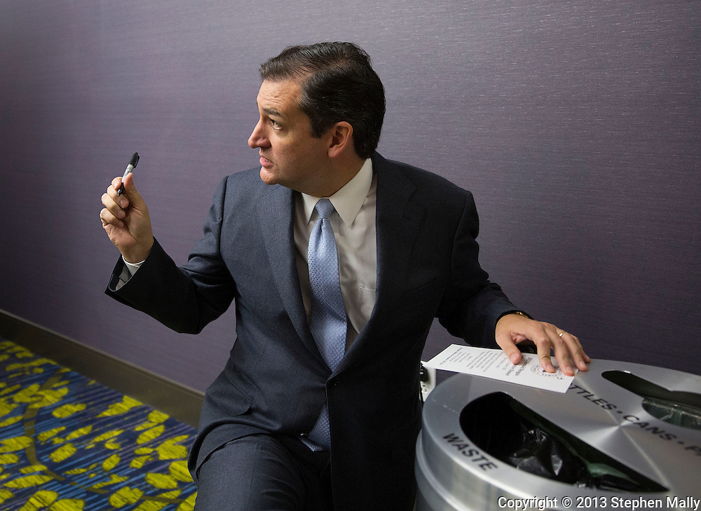DES MOINES, IA - OCTOBER 25, 2013: Senator Ted Cruz, Republican of Texas, kneels by a trashcan in the corner as he signs a program for Sarah Brooks (not pictured), 19, of Des Moines, Iowa before the start of the Iowa GOP Ronald Reagan Dinner at the Iowa Events Center - Community Choice Credit Union Convention Center in Des Moines, Iowa.