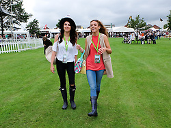 © Licensed to London News Pictures.14/07/15<br /> Harrogate, UK. <br /> <br /> Two girls walk across the grass near the bandstand on the opening day of the Great Yorkshire Show.  <br /> <br /> England's premier agricultural show opened it's gates today for the start of three days of showcasing the best in British farming and the countryside.<br /> <br /> The event, which attracts over 130,000 visitors each year displays the cream of the country's livestock and offers numerous displays and events giving the chance for visitors to see many different countryside activities.<br /> <br /> Photo credit : Ian Forsyth/LNP