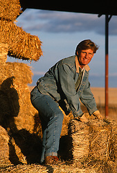 Man on a ranch in New Mexico moving a bale of hay