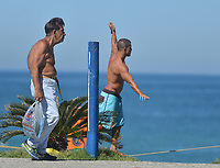 Rio de Janeiro-Brazil12 May 2020 man practices slackline at Barra da Tijuca beach, in the west of the city of Rio de Janeiro during quarantine and ban on walking without a mask