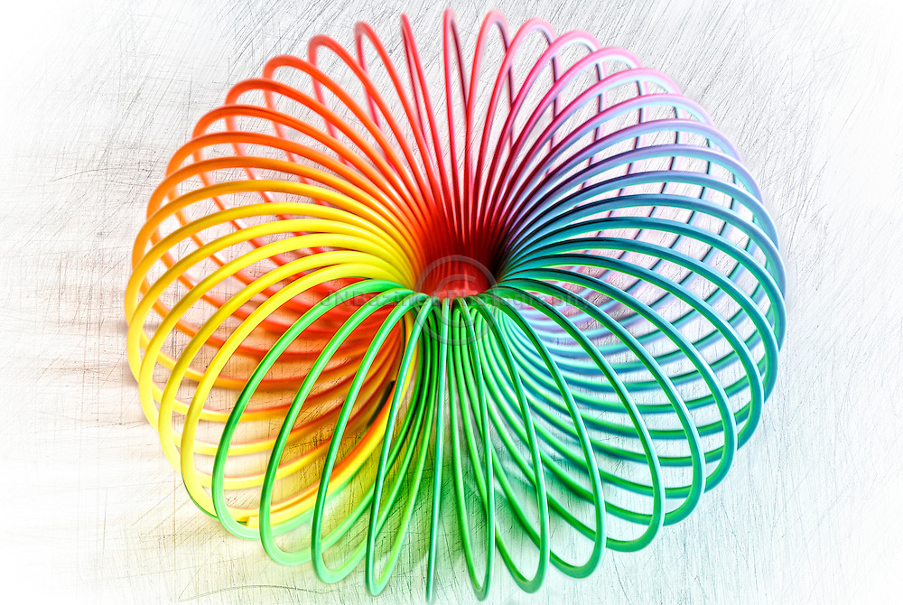 A fun, stylish photo of a slinky shaped into a ball.  Big, bold multicoloured and repeating lines set against crayon coloured background.