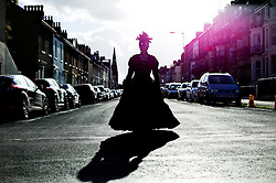 © Licensed to London News Pictures. <br /> 01/11/2014. <br /> <br /> Whitby, Yorkshire, United Kingdom<br /> <br /> Judith Young from Guisborough stands on a street as she poses for a pictures during the Whitby Goth Weekend. <br /> <br /> The event this weekend brings together thousands of extravagantly dressed followers of Victoriana, Steampunk, Cybergoth and Romanticism who all visit the town to take part in celebrating Gothic culture. This weekend marks the 20th anniversary since the event was started by local woman Jo Hampshire.<br /> <br /> Photo credit : Ian Forsyth/LNP