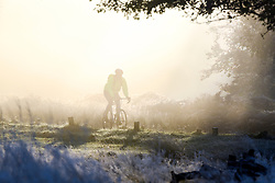 © Licensed to London News Pictures. 02/11/2016. Richmond, UK. A man cycles through the frosty scene. Deer in the frost in Richmond Park London today 2nd November 2016. much of the country experienced a frost overnight. Photo credit : Stephen Simpson/LNP