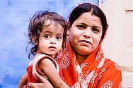 India, Jodhpur. Mother carrying a baby in the street of the old Jodhpur.
