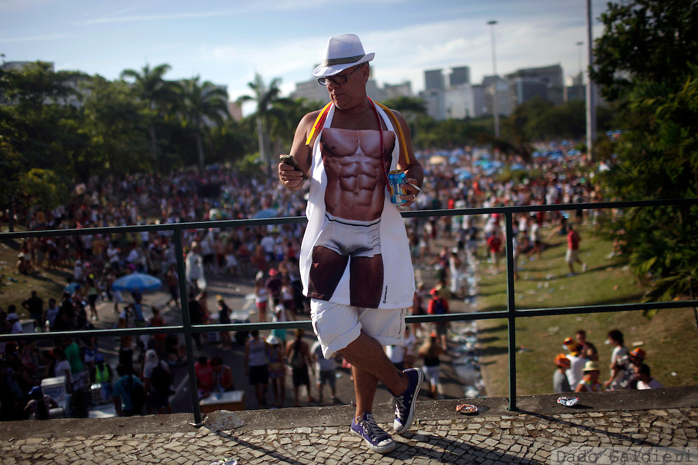 "A man wearing a buff man apron checks his smartphone on the periphery of the Beatles-themed street party, ""Sargento Pimenta,"" Portuguese for ""Sergeant Pepper,"" at the Aterro do Flamengo urban park in Rio de Janeiro, Brazil, Monday Feb. 20, 2012. The group that organizes the party gives the Beatles repertoire a Brazilian tweak, adapting ""All My Loving"" to the peppy beat of a traditional Carnival ""marchinha,"" or march, and infusing ""Hard Day's Night"" with a Rio funk sound. (AP Photo/Dado Galdieri)"