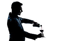 one caucasian man portrait pouring wine in a glass silhouette in studio isolated white background