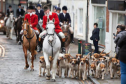 © Licensed to London News Pictures. 01/01/2019. Atherstone, North Warwickshire, UK. Atherstone Hunt arrive in the Market Square, Atherstone Town Centre, Warwickshire. The traditional New Year's Day Hunt starts at Noon with speeches and a drink for the Huntsmen and women. Riders of all ages took part in the meet and there were protests from Anti Hunt protestors who had positioned themselves in the centre of the Market Square. The Hunt then formed up and rode from the town centre passing huge New Year's Day crowds that had come to see the spectacle. Photo credit: Dave Warren/LNP