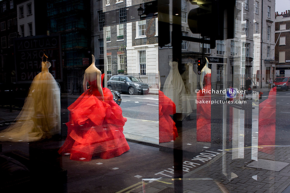 Red wedding dress on a mannequin stands in the window of couture retailer Vera Wang on Brook street, Mayfair, London.