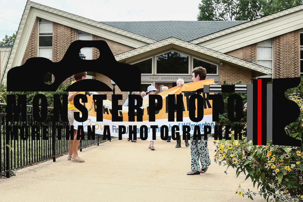 Members of the First Unitarian Church congregation hold a black lives matter banner during a rededication ceremony Sunday, August 21, 2016, at First Unitarian Church in Wilmington.