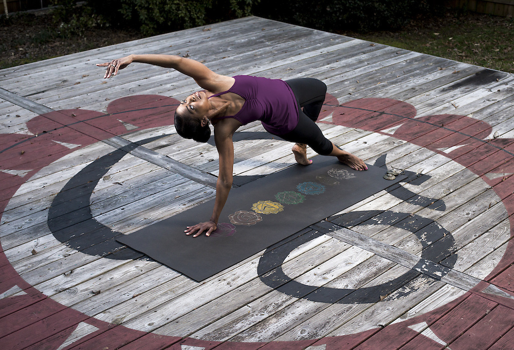 photograph of an african american woman practicing yoga outdoors.
