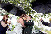 U.S. Army Spc. Patrick Intorre, right, and Janai Roberts kiss directly following their wedding ceremony while Shanna McMahon, left, and Zach Braun offer protection from the rain, in front of the W.W. Seymour Botanical Conservatory at Wright Park in Tacoma, October 11, 2011.  The couple selected Tuesday to wed since they consider eleven their lucky number. Pierce County District Court Judge Pat O'Malley, who officiated their marriage, selected the location after the couple were denied a mid-day marriage time by other judges.  Intorre's work schedule wouldn't accommodate 4pm--when courtrooms are available for marriages. Without a courtroom O'Malley offered to conduct the brief ceremony at noon under a tree at Wright Park.  And to make sure everyone found the same tree he suggested meeting in front of the Conservatory.(Janet Jensen/Staff photographer)