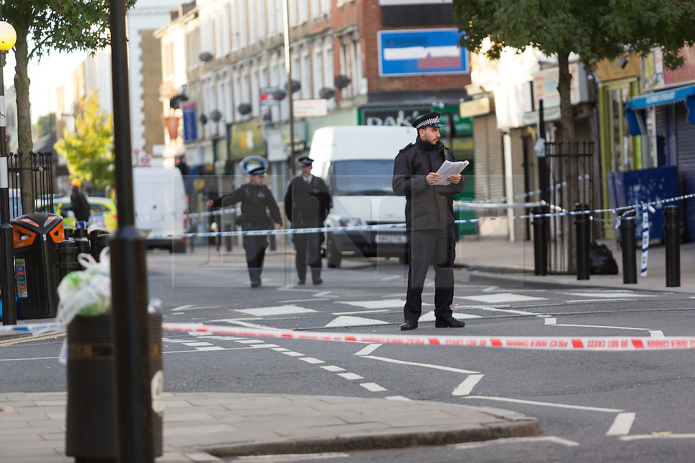 © Licensed to London News Pictures. 27/09/2015. London, UK. Police officers at the cordon on Chatsworth Road. Police have launched a murder investigation after a man was shot dead in the street outside Regal Pharmacy next to Mighty Meats butcher shop in Chatsworth Road, Hackney, east London yesterday. Photo credit : Vickie Flores/LNP