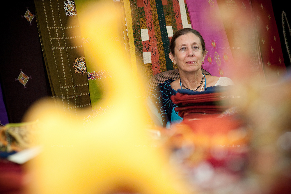 Judy Frater is an American anthropologist who has started a design school to teach villagers in Gujarat how to make traditional textiles. Here she is at the  Kala Raksha craft sale in Dehli selling her wares with some of the artisans she's trained.  (www.kala-raksha.org). New Delhi, October 2009