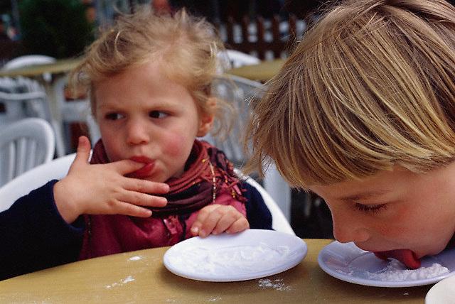 2001, Kanlica, Turkey --- Children Licking Powdered Sugar off Saucers --- Image by © Owen Franken/CORBIS