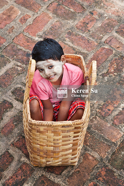 Girl with face painted white in basket, Bagan, Myanmar