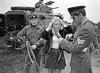 Julie Goodyear better known as Bet Lynch, landlady of Coronation Street's Rover's Return, arriving to open for army personnel a traditional English pub at Ballykinlar Army Camp, N Ireland, has her handbag security checked  after arriving in an army personnel carrier. 197212160826d, 825/72.<br /> <br /> Copyright Image from Victor Patterson, 54 Dorchester Park, Belfast, UK, BT9 6RJ<br /> <br /> t1: +44 28 9066 1296 (from Rep of Ireland 048 9066 1296)<br /> t2: +44 28 9002 2446 (from Rep of Ireland 048 9002 2446)<br /> m: +44 7802 353836<br /> <br /> victorpattersonbelfast@gmail.com<br /> victorpatterson@me.com<br /> <br /> www.victorpatterson.com<br /> <br /> Please see my Terms and Conditions of Use at https://www.victorpatterson.com/page2<br /> It is IMPORTANT that you familiarise yourself with them.<br /> <br /> Images used on the Internet incur an additional cost and must be visibly watermarked i.e. © Victor Patterson within the body of the image and copyright metadata must not be deleted. Images used on the Internet have a size restriction of 4kbs and are chargeable at rates available at victorpatterson.com.<br /> <br /> This image is available only for the use of the download recipient i.e. television station, newspaper, magazine, book publisher, etc, and must not be passed on to any third party. It is also downloaded on condition that each and every usage is notified within 7 days to victorpatterson@me.com<br /> <br /> The right of Victor Patterson (or the named photographer) to be identified as the author is asserted in accordance with The Copyright Designs And Patents Act (1988). All moral rights are asserted.