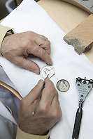 Top view of a mature worker repairing watch