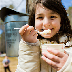 A girl (age 8) enjoys a maple sundae at Folsom's Sugar House in Chester, New Hampshire.