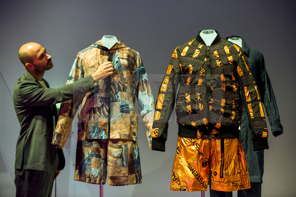 "© Licensed to London News Pictures. 17/10/2019. LONDON, UK. A staff member views ""Mars clothing, SS20 New Horizons collection"", by Raeburn. Preview of ""Moving to Mars"" at the Design Museum. The exhibition explores how sending humans to Mars is a frontier for science as well as design and features over 200 exhibits from NASA, the European Space Agency together with new commissions.  The show is open 18 October to 23 February 2020.  Photo credit: Stephen Chung/LNP"