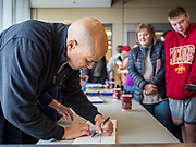 27 NOVEMBER 2019 - DES MOINES, IOWA: US Senator CORY BOOKER (D-NJ) signs an autograph for a volunteer after lunch at Central Iowa Shelter and Services in Des Moines. They had to bump elbows rather than shake hands because Sen Booker was wearing gloves to handle food. Sen Booker helped plate up and serve lunch at the shelter. The shelter has about 180 beds and is full almost every night. In January and February, more than 250 people per night come to the shelter, which sets out overflow bedding. Senator Booker is running to be the Democratic nominee for the US Presidency in 2020. Iowa hosts the first selection event of the presidential election season. The Iowa caucuses are February 3, 2020.        PHOTO BY JACK KURTZ