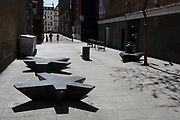 At the beginning of the fourth week of the UK government's lockdown during the Coronavirus pandemic, and with 120,067 UK reported cases with 16,060 deaths, just two Londoners walk down Ramillies Street while another sits in the sunshine in an otherwise deserted West End of London, on 20th April 2020, in London, England.