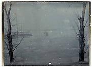 during winter flooded low laying land with trees and halve under water buildings , flood Seine River Paris January 1910