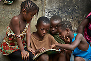 Children read at a home in Magburaka, Tonkolili district, Sierra Leone on March 25, 2017.
