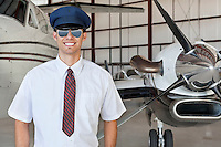 Portrait of handsome young pilot standing in front of airplane